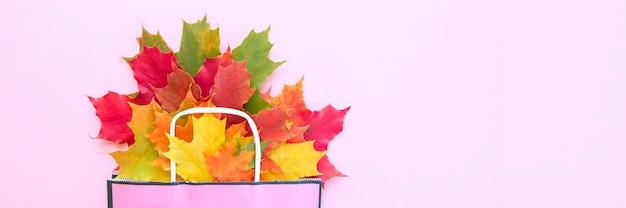 秋のセール。秋のカエデの葉と紙袋。