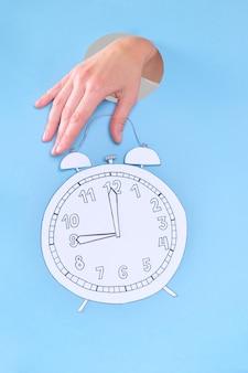 青の目覚まし時計を持っている女性の手。