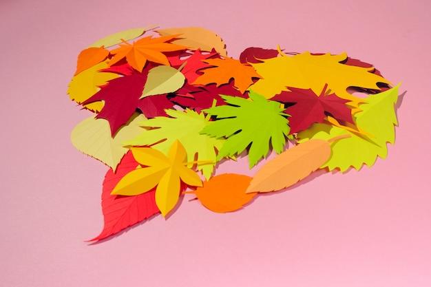 紙の葉が赤、オレンジ、黄色の葉に落ちる。