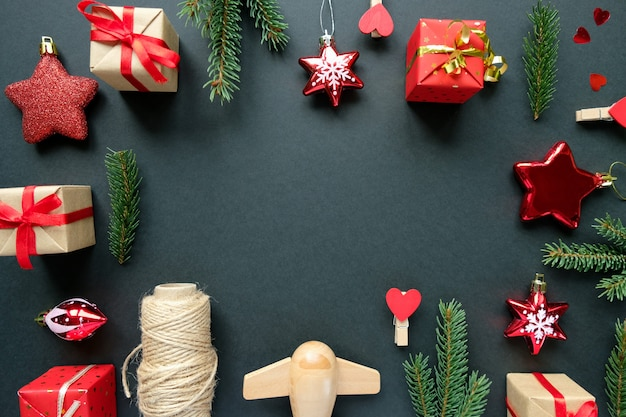 枝、星、黒いフレームの背景にギフトボックスとクリスマスの装飾