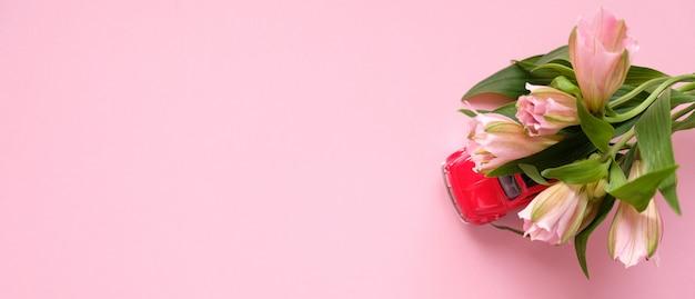 Маленькая красная игрушечная машинка несет букет розовых цветов