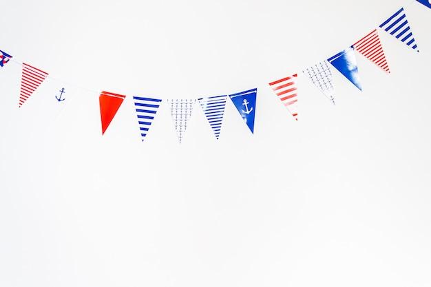 白い背景の上の紙で作られたカラフルなパーティーフラグ