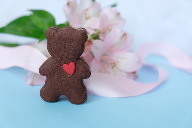 Печенье в форме медведя с розовой лентой на розовом фоне.