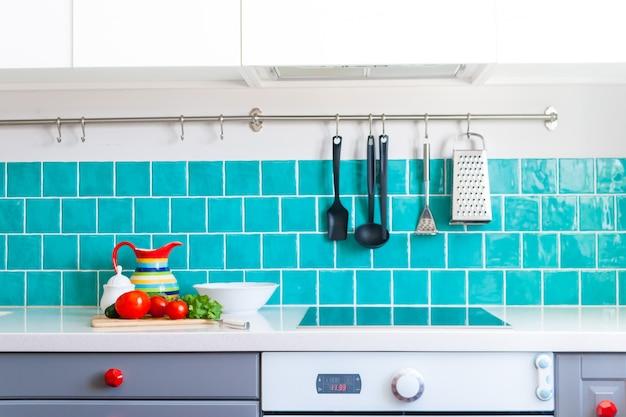 キッチンには、白いクォーツカウンタートップと光沢のある青いケアタイルを組み合わせたダークグレーのフラットフロントキャビネットが備わっています。