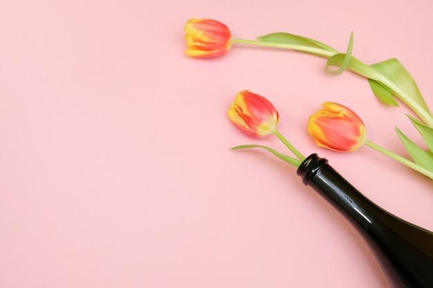 Цветы в бутылке на розовом фоне.