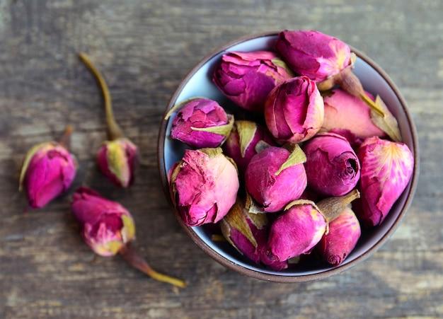 古い木製のテーブルの上にボウルにバラのつぼみの花を乾燥させます。健康的なハーブドリンクのコンセプト