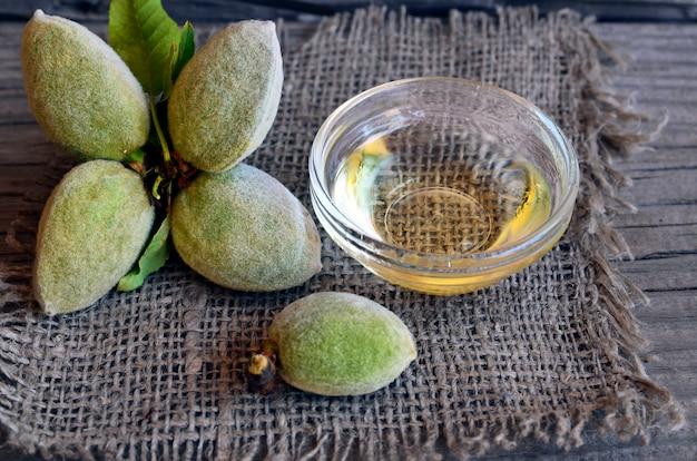 アーモンドナッツと古い木製の背景にガラスのボウルにアーモンドオイルの枝。選択と集中。