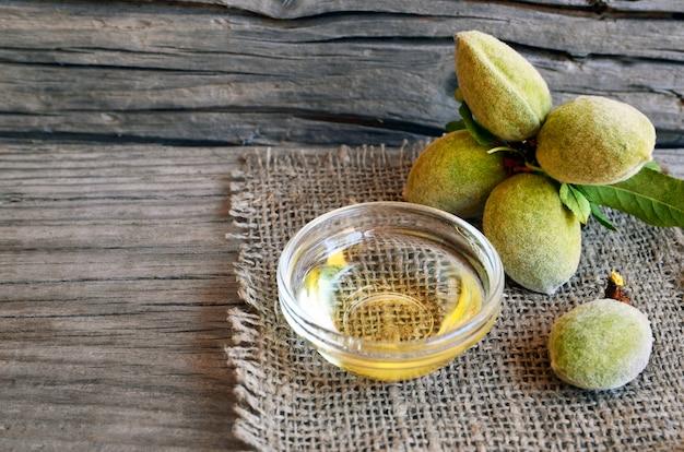 アーモンドナッツと古い木製の背景にガラスのボウルにアーモンドオイルの枝。