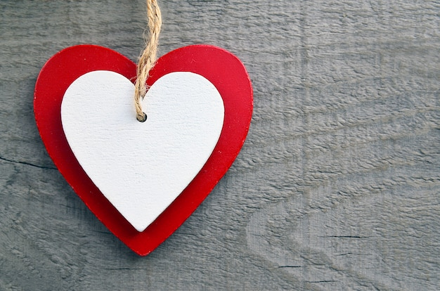 灰色の木製の背景に装飾的な赤と白の木製ハート。聖バレンタインの日や愛の概念。