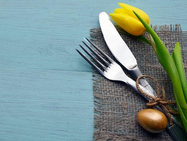 黄色のチューリップ、金の卵、コピースペースを持つ青い木製の背景にカトラリーとイースターテーブルの設定。春のテーブルの設定。イースターディナーの装飾。ハッピーイースターのコンセプト。選択と集中。