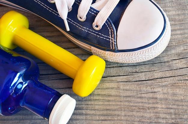 フィットネス機器。青い水のボトル、黄色のダンベル、木製の背景にスニーカー。健康的なライフスタイル、スポーツ、フィットネスのコンセプト。