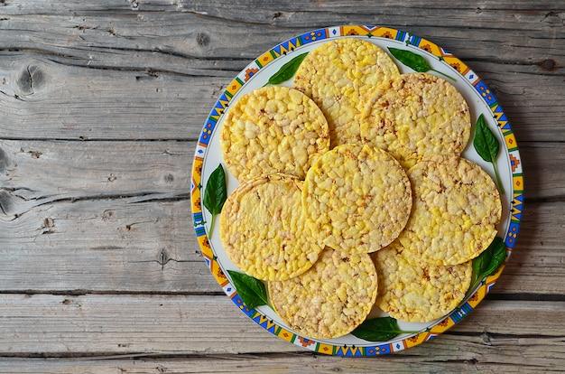 ほうれん草と全粒粉クリスプブレッドは、古い木製のテーブルのプレートに残します。健康的な朝食や食事のコンセプトです。