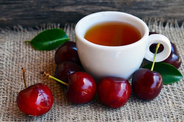 黄麻布の上にガラスの透明なカップで採れたての熟したチェリーとお茶。