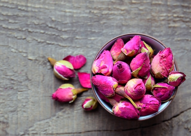 古い木製のテーブルの上にボウルにバラのつぼみの花を乾燥します。