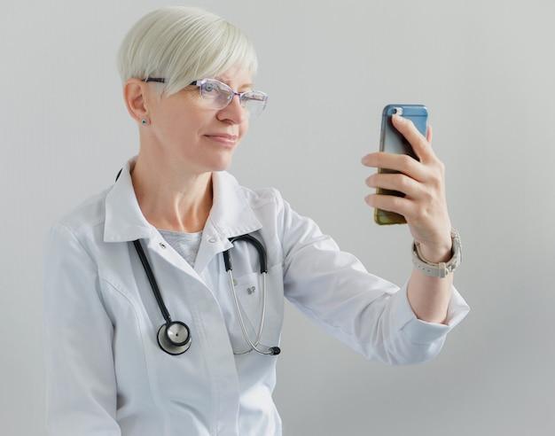 医師は携帯電話でビデオ通話をしています。ビデオ会議。診療所とオンライン患者受付