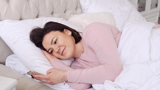 ベッドに横たわっている間携帯電話を使用している女性。良いニュース、笑顔でメールを書いたり、ソーシャルメディアをチェックしたりするメッセージを受け取りました。