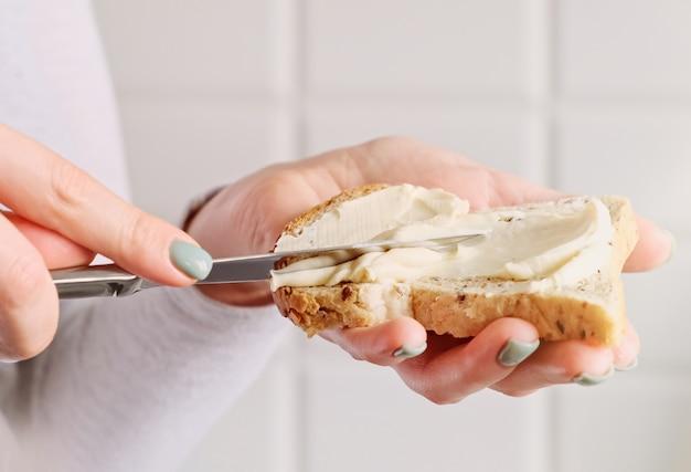 Женские руки, делая бутерброд. женщина готовит завтрак, положить сыр на тост хлеб.