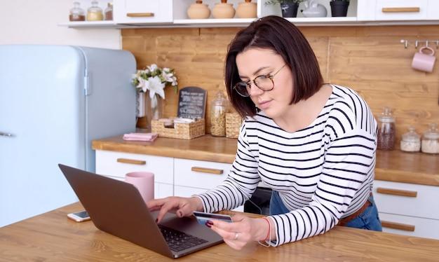 ノートパソコンでのオンラインバンキング。自宅の台所でクレジットカードでオンラインショッピングをしている女性。デジタルガジェットを使用して簡単に支払う。