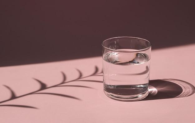 明るい太陽に照らされたコップ一杯の水。ピンクのテーブルに液体が入った透明な容器。ハードシャドウ。