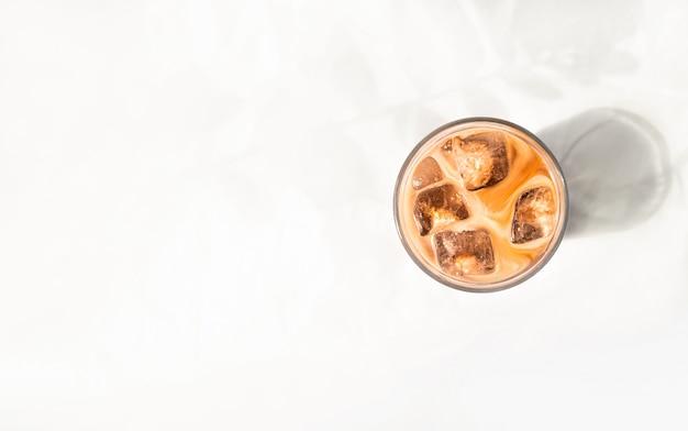 白いベッドで牛乳とアイスコーヒーのカップ。