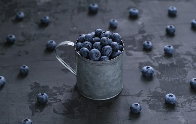 暗闇の中で鉄のマグカップで新鮮なブルーベリーの果実