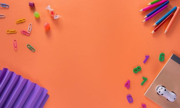 オレンジ色の背景に色の異なる学用品。学校の背景に戻る。フラット横たわっていた、トップビュー