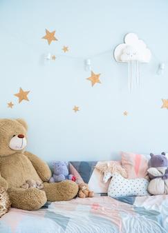 Интерьер детской спальни выполнен в голубых тонах. детские игрушки и декор комнаты для детей.