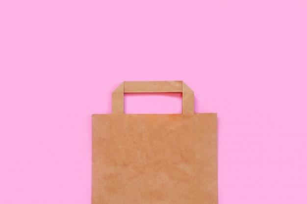 ピンクの背景の紙袋。リサイクルとプラスチック廃棄