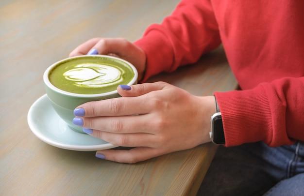 ビーガン野菜の牛乳と緑の抹茶ラテを飲むカフェの女性