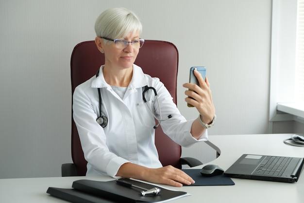 医師は携帯電話でビデオ通話をしています。ビデオ会議。医院およびオンライン患者受付