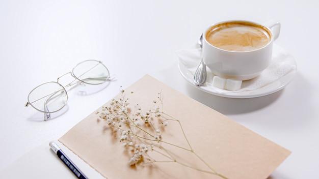 На белом столе - чашка кофе, стаканы, блокнот с карандашом и белый цветок.
