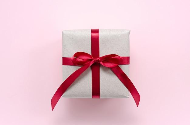 リボンが付いた赤いサテンのリボンが付いた、リサイクルされた廃棄物からの環境に優しい紙の紙で包まれたギフト
