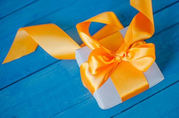 Подарочная коробка с бантиком на деревянном столе