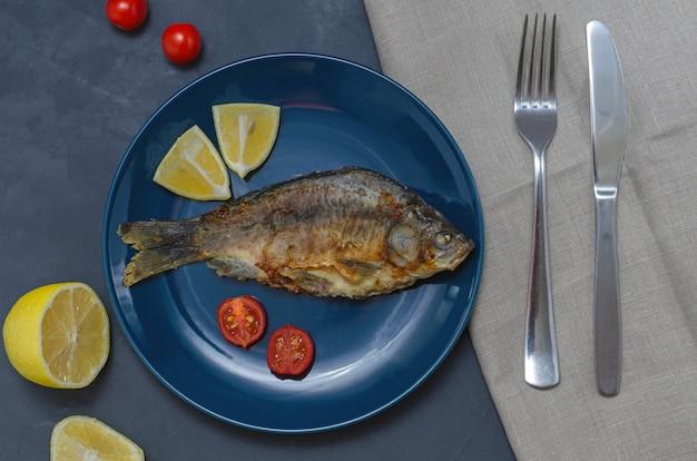 ナイフとフォークでトマトとレモンのスライスで飾られた灰色のテーブルの青い皿に調味料と食欲をそそる魚フナを揚げた。健康的な食事のコンセプト。