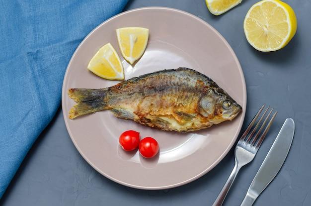 Жареная карась из аппетитной рыбы с приправой на бежевой тарелке на сером столе, украшенном ломтиками помидора и лимона с ножом и вилкой. концепция здорового питания.