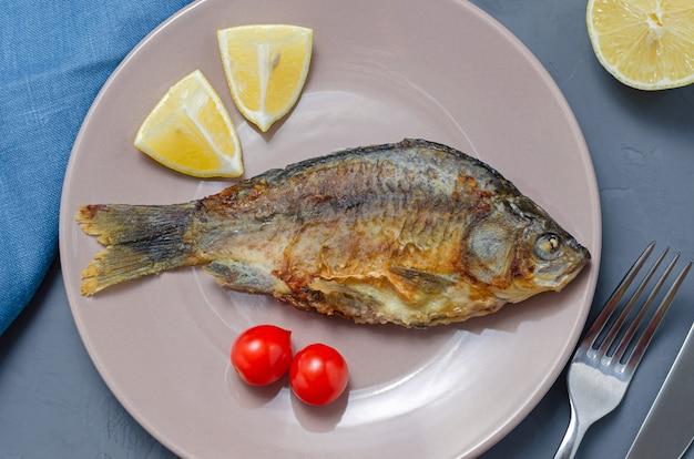 ナイフとフォークでトマトとレモンのスライスで飾られた灰色のテーブルの上のベージュプレートに調味料と食欲をそそる魚フナのフライ。健康的な食事のコンセプト。