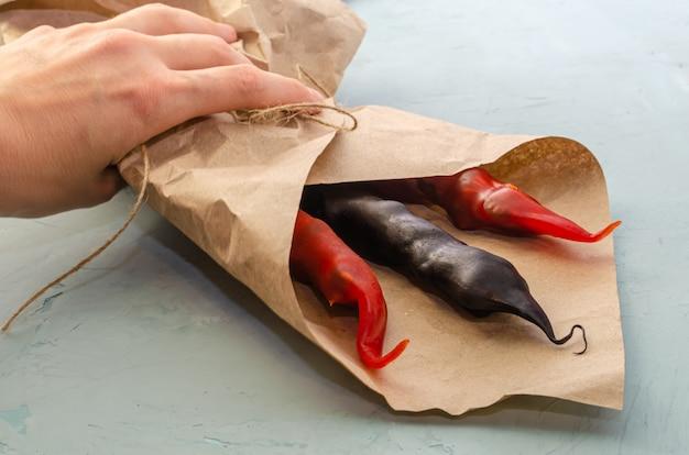 Рука берет букет из разноцветных чурчхел в натуральной упаковке с джутовой веревкой на светлом столе с местом для текста. здоровый образ жизни.