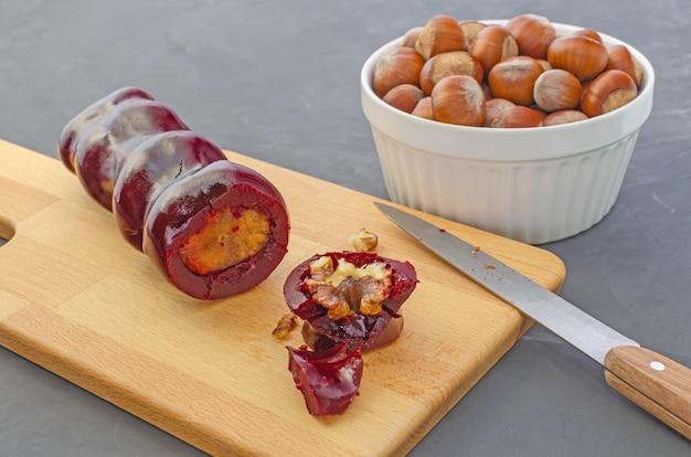 Нарезанный чурчхела с фундуком, инжир и грецкие орехи на разделочную доску, на темном столе. восточная сладость