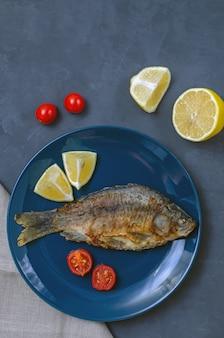 ナイフとフォークでトマトとレモンのスライスで飾られた灰色のテーブルの青い皿に調味料と食欲をそそる魚フナを揚げた。コピースペース。