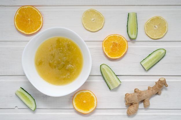 Варенье из огурцов с дольками апельсина, лимона и имбиря на светлом деревянном столе. концепция здорового питания.