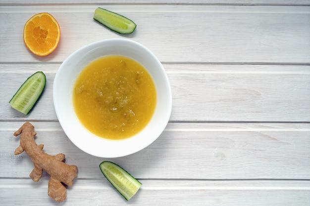 Варенье из огурцов с кусочками апельсина, лимона и имбиря на светлом деревянном фоне. концепция здорового питания.