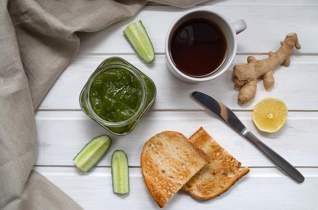 Варенье из зеленых огурцов в прозрачной банке с ломтиками огурца и имбиря с тостами, ножом и текстильной салфеткой на светлом деревянном столе. концепция здорового питания.