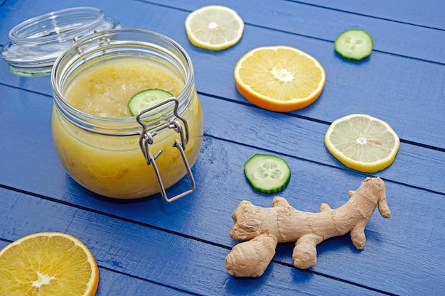 Варенье из огурцов в стеклянной банке с кусочками ингредиентов апельсина, лимона, огурца и имбиря на синем деревянном столе