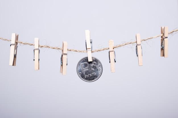 Монета с символом российского рубля висит на деревянных прищепках на белом фоне