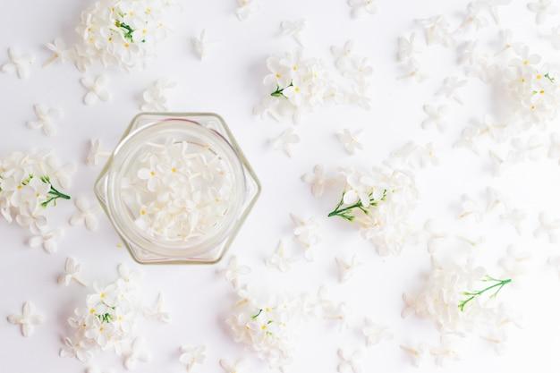 Белые цветы черемухи в прозрачной стеклянной банке на белом