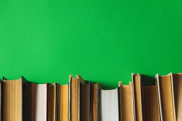 背景が緑色の棚の上の古い本