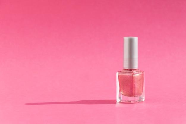 Стеклянная бутылка лака для ногтей на розовом фоне