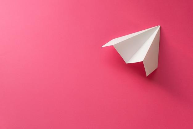 Белый бумажный самолетик на розовом фоне