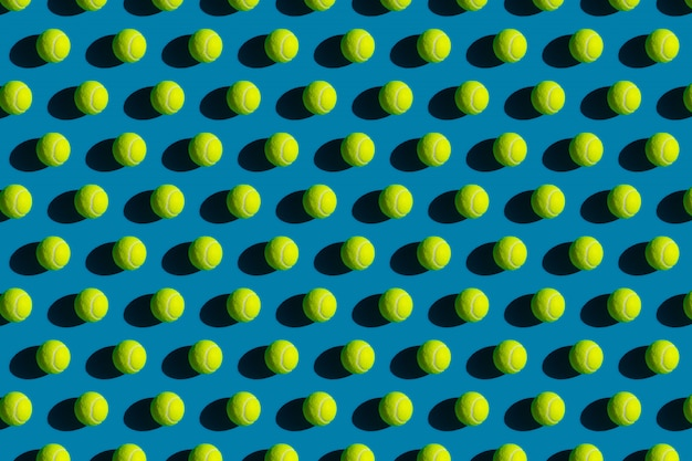 Геометрический рисунок теннисных мячей с сильными тенями на синем