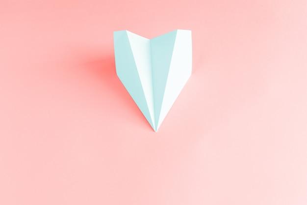 サンゴの背景に淡いブルーの紙飛行機。